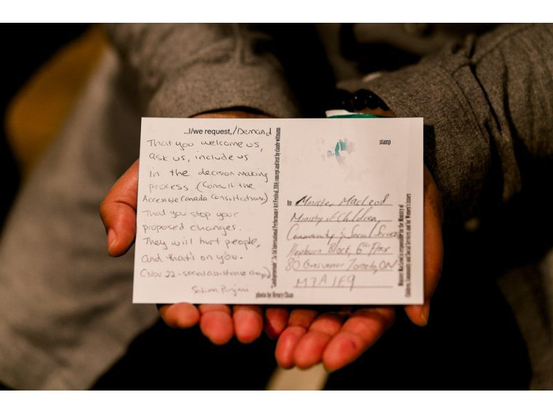 A photo of hands holding a postcard from claud's performance.