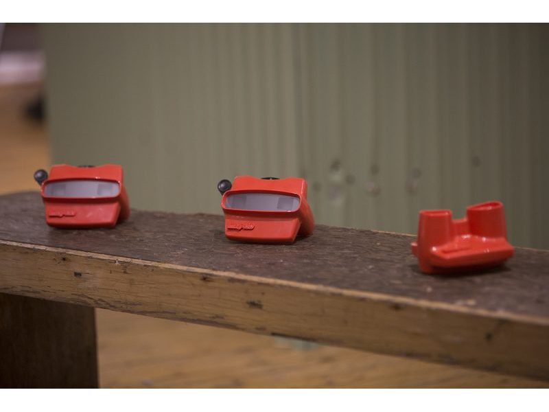 Three red kaleidoscopes on wooden bench