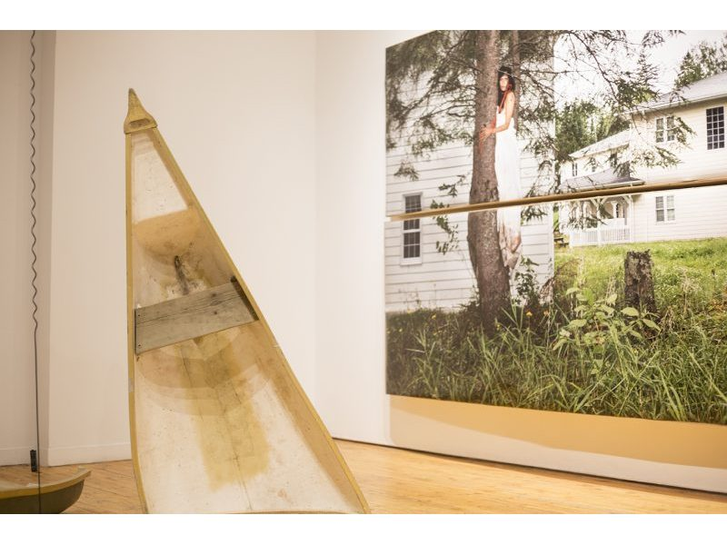 A canoe cut in half and propped upright on gallery floor pointing upwards.