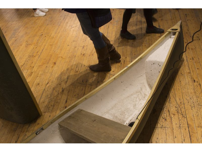 Half of a canoe lying on gallery floor