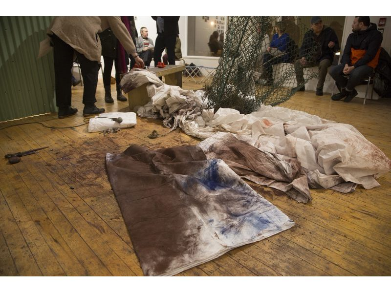 White sheets covered in rusted pastel on gallery floor