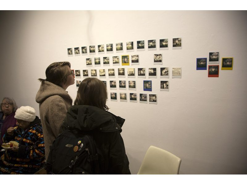 Polaroid photos hanging on gallery wall
