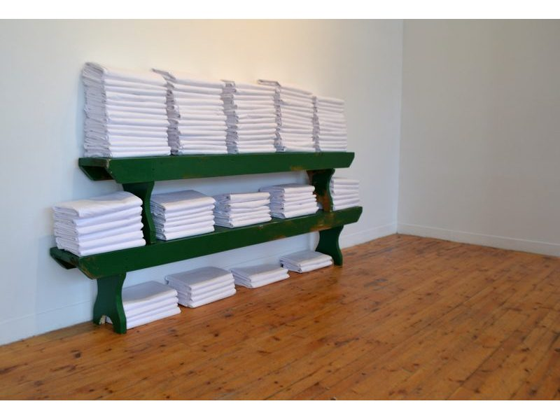 Piles of folded white bed sheets on shelves