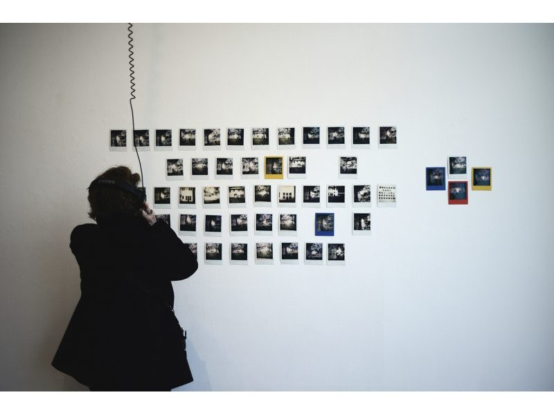 Polaroid photos hanging on a gallery wall