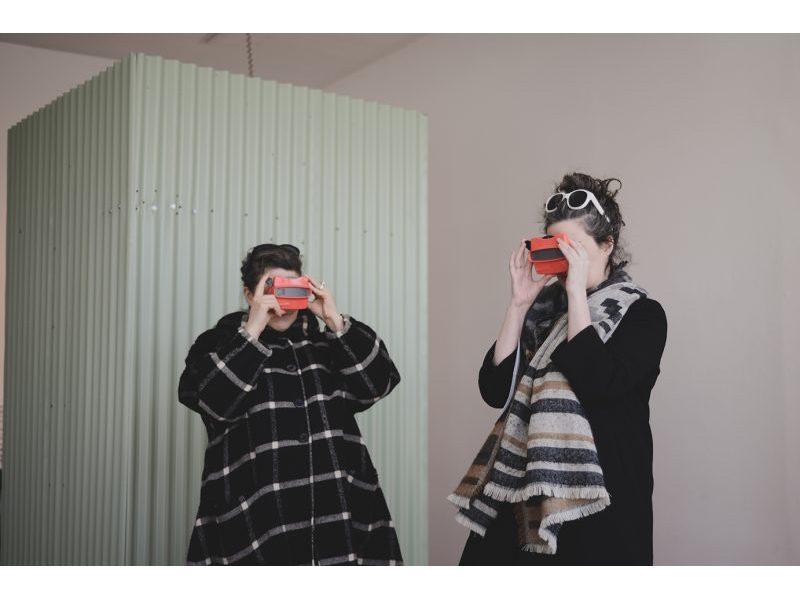Two people looking through kaleidoscopes